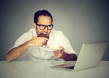 hombre comiendo: Estudiante del hombre joven que come mientras se trabaja en la computadora portátil