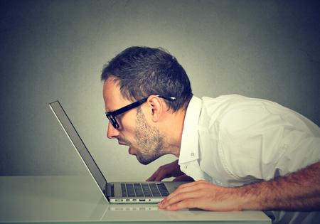 Perfil lateral hombre mirando de cerca intensamente la pantalla del portátil