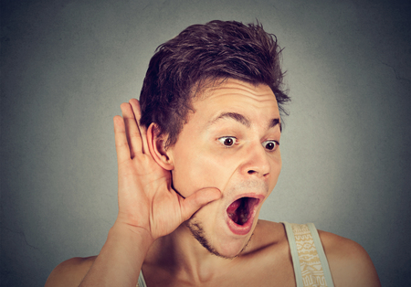chitchat: Closeup portrait surprised young nosy man hand to ear gesture carefully secretly listening gossip conversation news isolated grey background. Human face expression. Privacy violation Stock Photo