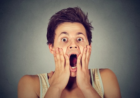 funny face: shocked surprised young man in full disbelief with hands on face screaming
