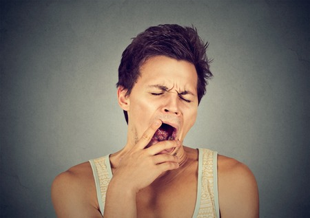 sleepy man: Young sleepy man yawning stretching arms back isolated on gray wall background. Sleep deprivation, burnout, laziness concept Stock Photo