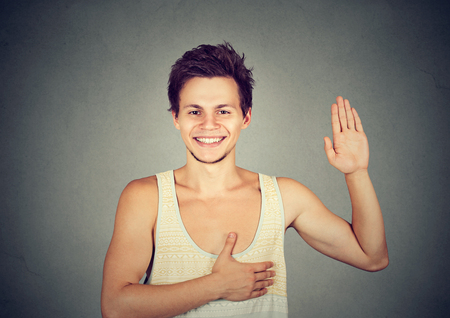 promise: Young happy smiling man making a promise Stock Photo