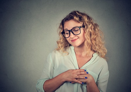 awkward: Lack of confidence. Shy young woman feels awkward isolated on grey wall background. Human emotion body language life perception Stock Photo
