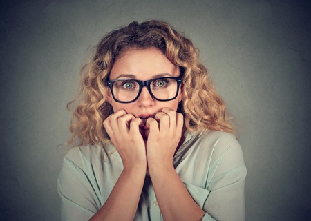 perfectionist: Closeup portrait nervous stressed young woman biting fingernails looking anxiously craving isolated gray background. Human emotion face expression feeling