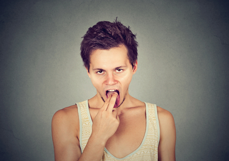 bad manners: disgusted man with finger in mouth displeased ready to throw up isolated on gray background. Human face expression, emotion Stock Photo