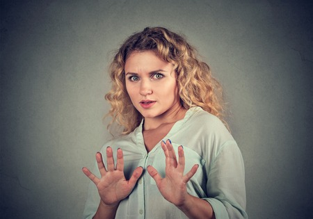 scared woman raising hands up in defense afraid about to be attacked or avoiding unpleasant situation, isolated on gray background. Negative human emotion facial expression feeling