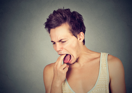 throw up: disgusted man with finger in mouth displeased ready to throw up isolated on gray background. Human face expression, emotion Stock Photo