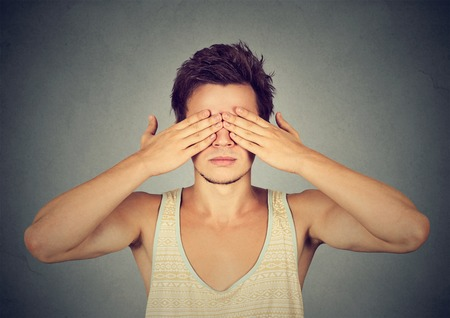 withhold: man covering eyes with hands cant see, hiding, isolated on gray background
