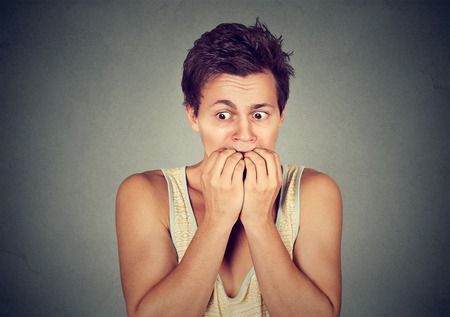 freak out: Portrait anxious young man biting his nails fingers freaking out