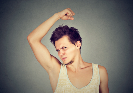Closeup portrait of young man, smelling, sniffing his armpit, something stinks, very bad, foul odor situation, isolated on gray wall background. Negative emotion, facial expression, feeling