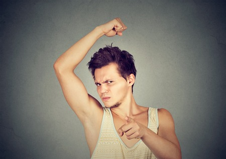 intolerable: Closeup portrait of young man, smelling, sniffing his armpit, something stinks, bad, foul odor, pointing finger at camera isolated on gray background. Negative emotion, facial expression, feeling