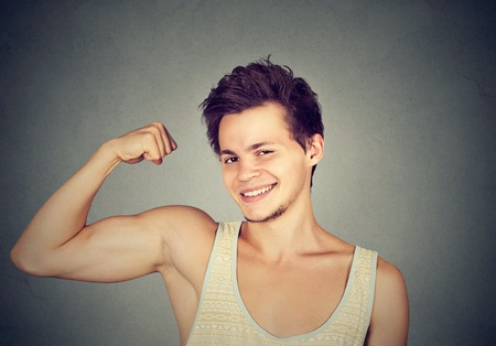 boy muscles: Fit and muscular young man flexing his biceps isolated on gray background