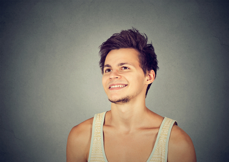 daydreaming: Happy man daydreaming looking up isolated on gray background Stock Photo