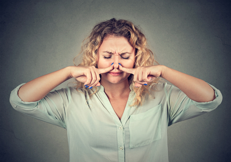 stinks: Closeup portrait woman pinches nose with fingers looks with disgust something stinks bad smell isolated on gray wall background. Human face expression body language reaction