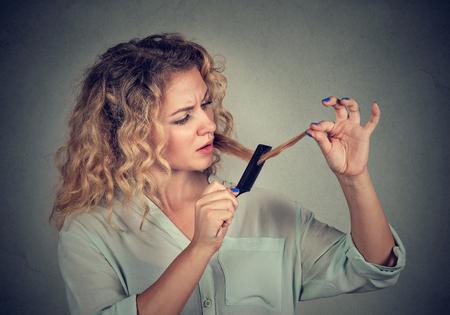 Die unglückliche frustrierte junge Frau der Nahaufnahme, die sie überrascht wird, verliert Haar, bemerkte geteilte Haarlücke der aufgeteilten Enden. Grauer Hintergrund. Menschliches Gesicht Ausdruck Emotion. Schönheit Frisur Konzept