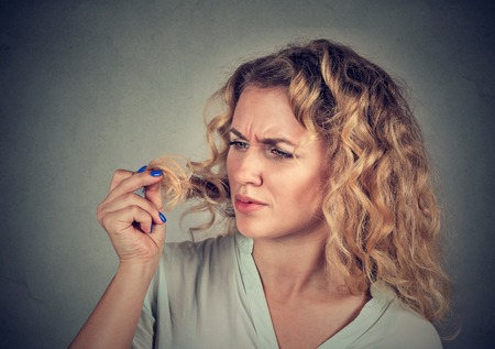 hair conditioner: unhappy frustrated young woman surprised she is losing hair, receding hairline. Gray background. Human face expression emotion. Beauty hairstyle concept