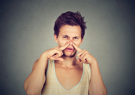 pinches: disgusted man pinches nose with fingers looks with disgust something stinks bad smell isolated on gray background. Human face expression body language reaction
