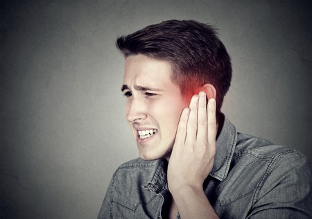 dolor de oido: Tinnitus. Closeup up side profile sick male having ear pain touching his painful head isolated on gray background Foto de archivo