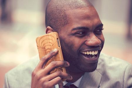 Primer guapo feliz riendo joven empresario hablando por teléfono móvil al aire libre. Efecto de filtro de Instagram