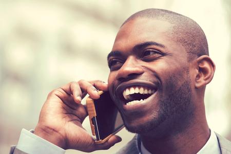 Primer guapo feliz riendo joven empresario hablando por teléfono móvil al aire libre.