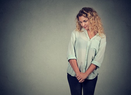 lack of confidence: Shy insecure young woman looking down avoiding eye contact standing isolated on gray wall background