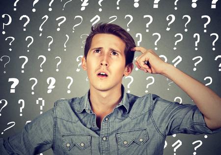 사려 깊은 혼란스러운 잘 생긴 남자가 너무 많은 질문을 가지고 있고 머리에 긁적 인 대답이 없다.