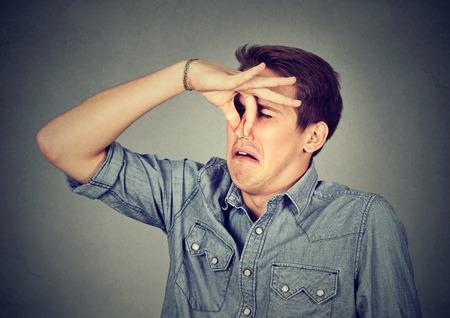 남자 손가락으로 코 pinches 혐오 뭔가 보이는 악취 나쁜 냄새 회색 배경에 고립. 인간의 얼굴 표현 신체 언어 반응