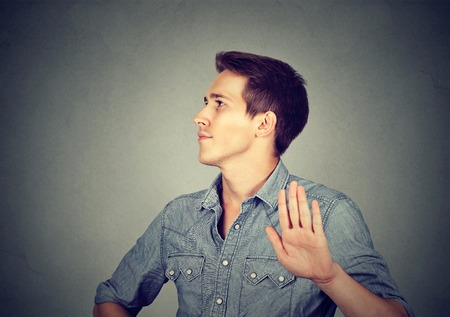 bad attitude: Closeup portrait young annoyed angry man with bad attitude giving talk to hand gesture with palm outward isolated grey wall background. Negative human emotion face expression feeling body language