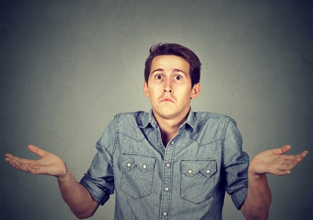 i don't know: Ignorance and arrogance. Closeup portrait young man shrugging shoulders who cares so what I dont know gesture isolated on gray wall background. Human body language. Whatever attitude reaction