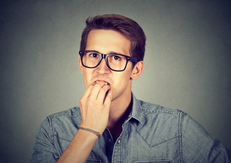 perfectionist: Preoccupied anxious young man biting fingernails nervously Stock Photo