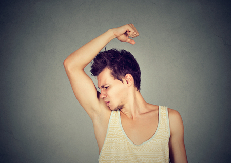 foul: Closeup portrait of young man, smelling, sniffing his armpit, something stinks, very bad, foul odor situation, isolated on gray wall background. Negative emotion, facial expression, feeling
