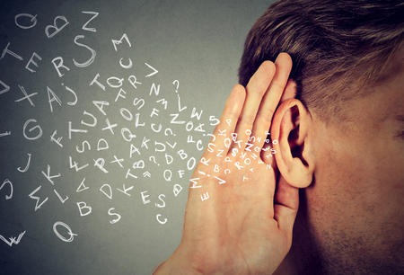 Mann hält seine Hand in der Nähe Ohr und hört aufmerksam Buchstaben des Alphabets in isoliert auf grau Wand Hintergrund fliegen