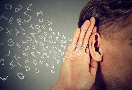 comunicação: O homem segura sua mão perto da orelha e escuta cuidadosamente as letras do alfabeto voando isoladas no fundo da parede cinza Banco de Imagens