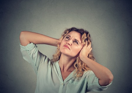 negative emotion: Young annoyed, unhappy, stressed woman covering her ears, looking up isolated grey background. Negative emotion reaction Stock Photo