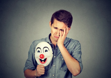 expressive: Young sad man with happy clown mask isolated on gray wall background. Human emotions