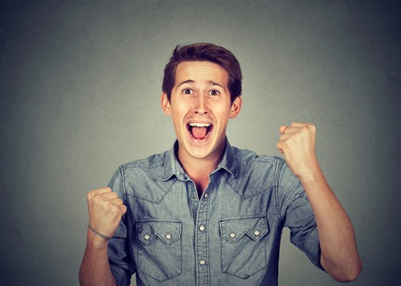 jubilate: Happy successful student, man winning, fists pumped celebrating success isolated grey background. Positive human emotion facial expression. Life perception, achievement Stock Photo