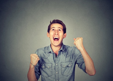 success man: Happy successful student, man winning, fists pumped celebrating success isolated grey background. Positive human emotion facial expression. Life perception, achievement Stock Photo