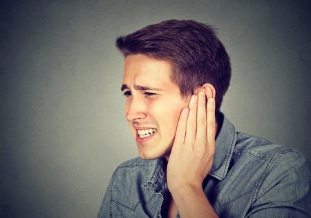 dolor de oido: Tinnitus. Portarretrato encima de perfil lado masculino enfermo que tiene dolor de oído tocar su dolorosa cabeza aislada sobre fondo gris