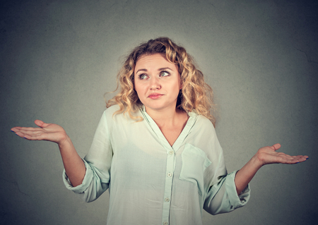 i don't know: Portrait dumb looking woman arms out shrugs shoulders who cares so what I dont know isolated on gray wall background. Negative human emotion, facial expression body language life perception attitude Stock Photo