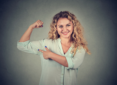 woman muscle: Closeup portrait young happy woman flexing muscles showing her strength isolated on grey wall background. Positive emotion facial expression feeling. Weight loss wellbeing concept