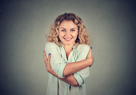 self conceit: Smiling woman holding hugging herself isolated gray wall background. Positive human emotion, facial expression, feeling, attitude. Love yourself concept