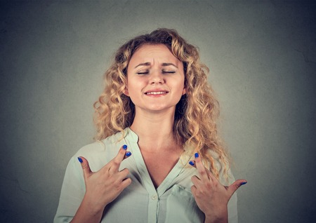 Closeup portrait hopeful beautiful woman crossing her fingers, eyes closed, hoping, asking best isolated on gray wall background. Human face expression, emotions, feeling attitude reaction