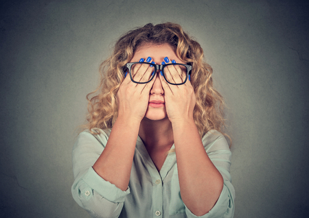 eyesight: Closeup portrait young woman in glasses covering face eyes using her both hands isolated on gray wall background