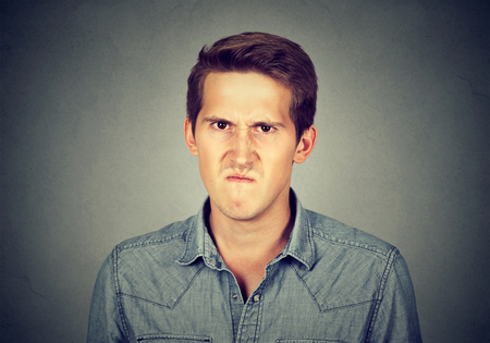 detestable: Angry young man, about to have nervous breakdown frustrated isolated on gray wall background. Negative human emotion facial expression feelings attitude