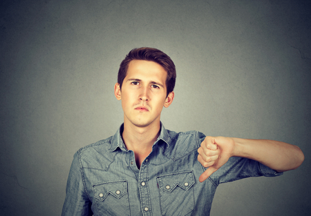 skeptic: Closeup portrait angry young man showing thumbs down sign, in disapproval isolated on gray background. Negative human emotion facial expression feelings Stock Photo
