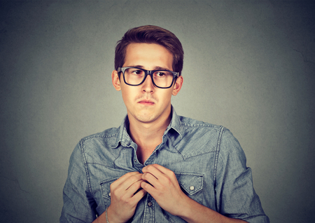 awkward: Nervous introvert man feels awkward looking anxiously away isolated gray wall background. Stock Photo