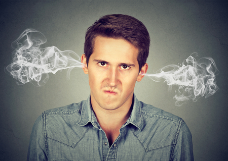 Closeup portrait of angry young man, blowing steam coming out of ears, about to have nervous breakdown isolated gray background. Negative human emotions facial expression feelings attitude