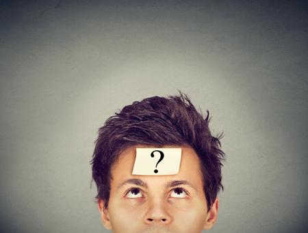 L'homme pensant avec point d'interrogation sur fond gris mur Banque d'images - 64447020