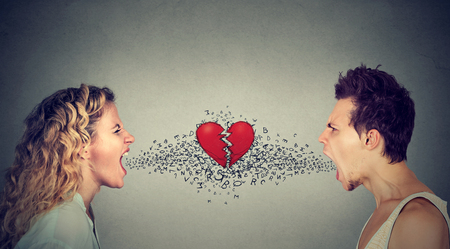 Side profile young man and woman screaming at each other with alphabet letters coming from mouth and broken heart in-between isolated on gray wall background