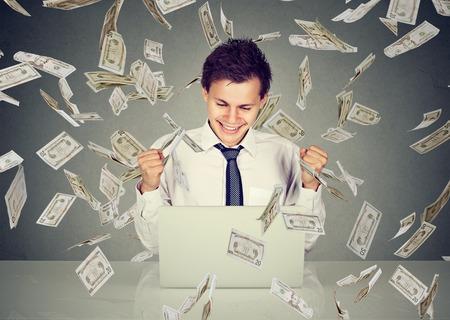 Online Business: Young man using a laptop building online business making dollar bills cash falling down. Beginner IT entrepreneur under money rain. Success economy concept Stock Photo